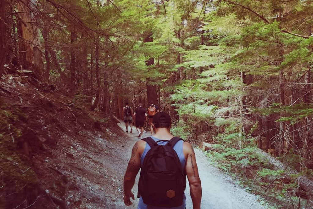 A man with tattoos wearing a backpack walks behind a row of people in a forest