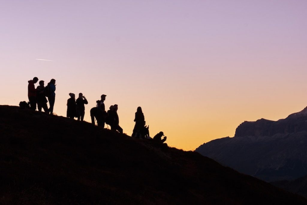 A group of people at sunrise or sunset standing on a large hill with a purple and orange sky in the background
