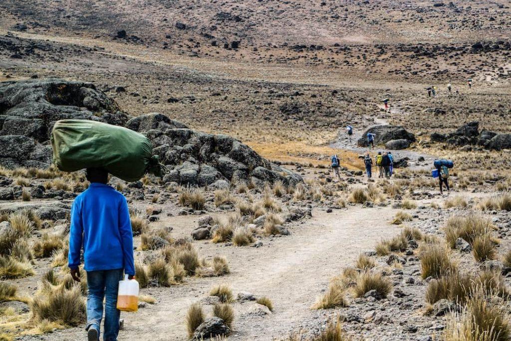 A guide balancing a bag on his head on Mount Kilimanjaro, Tanzania