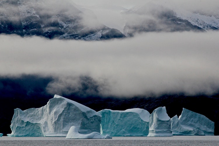 An iceberg in Greenland sits below the mist