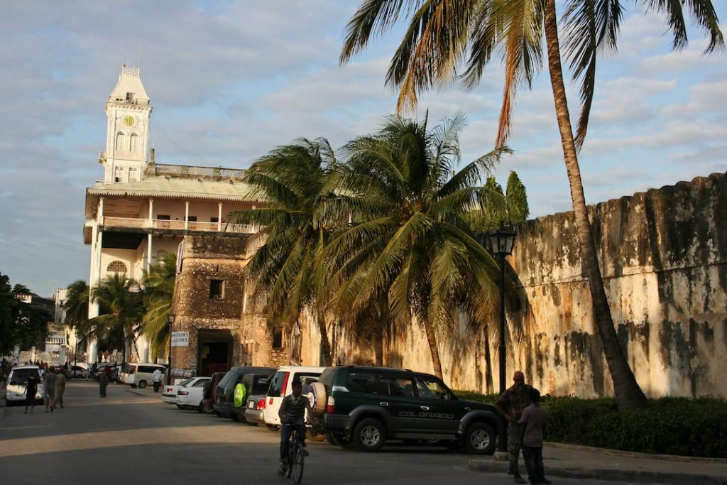 an old building and palm trees in Stone Town, Tanzania