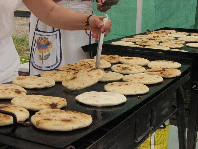 A person cooking pupusa, traditional food of El Salvador