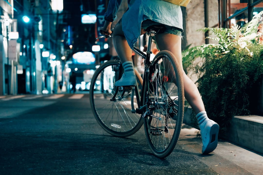 a person kicking off a bike on a busy city street at night