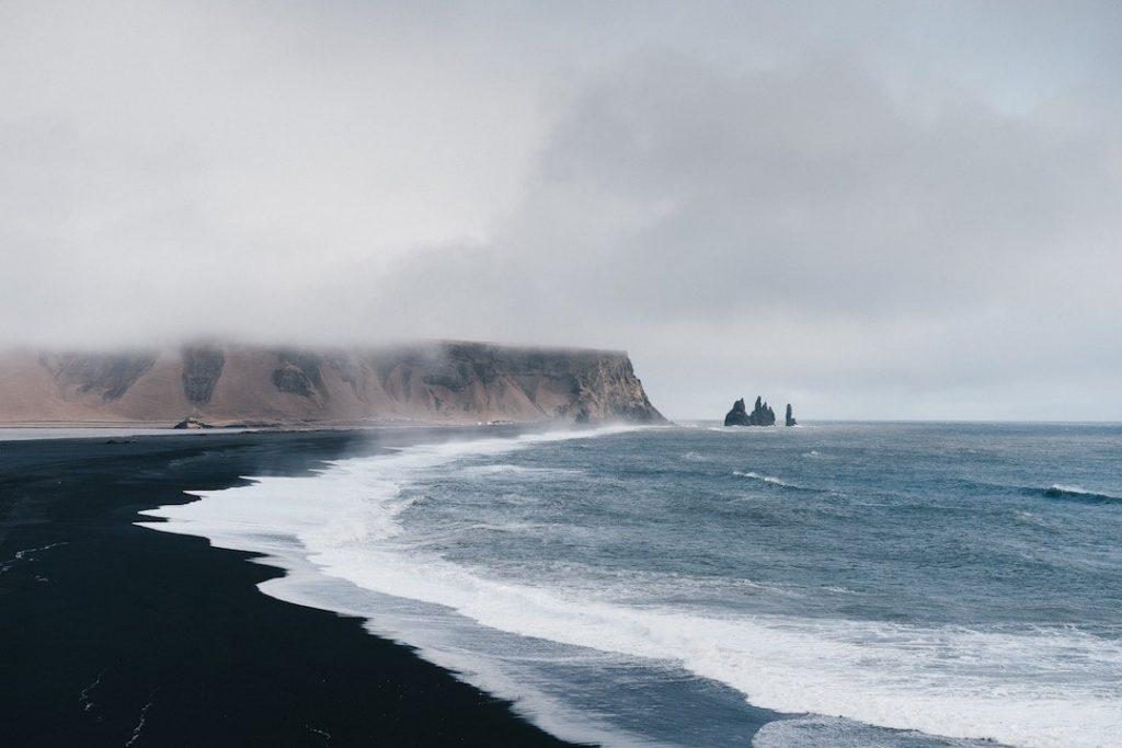 A black sand beach in Vik, Iceland on a foggy day