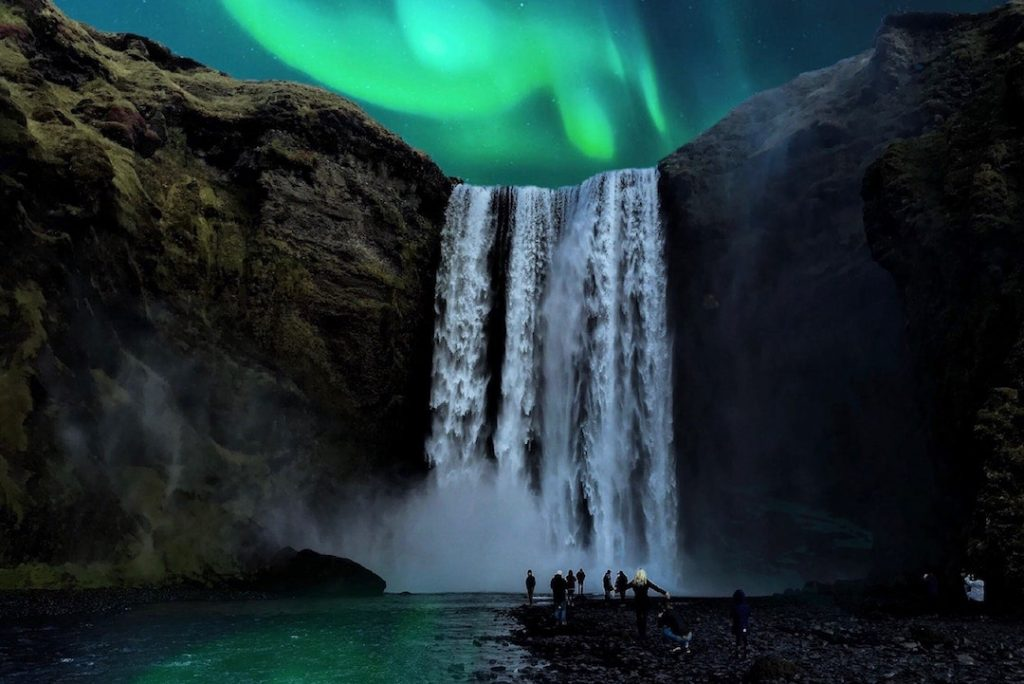 A group of people stand under Skógafoss in Iceland with the Northern Lights above