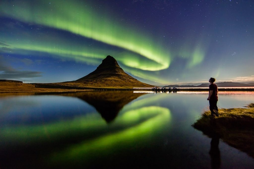 A man stands by a lake and stares up at the Northern Lights in Iceland