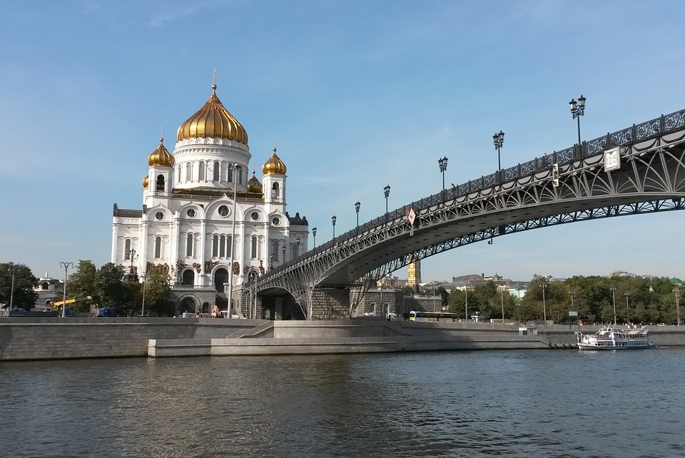 view of a golden domed white cathedral from the river