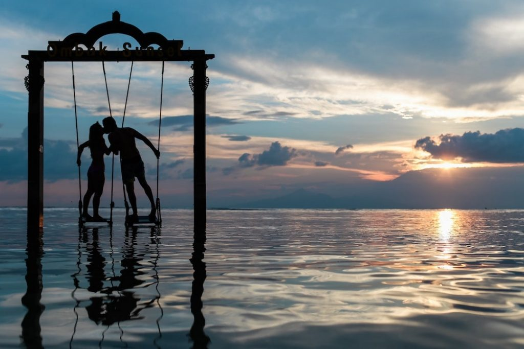 A couple on a swing over the ocean kiss at sunset