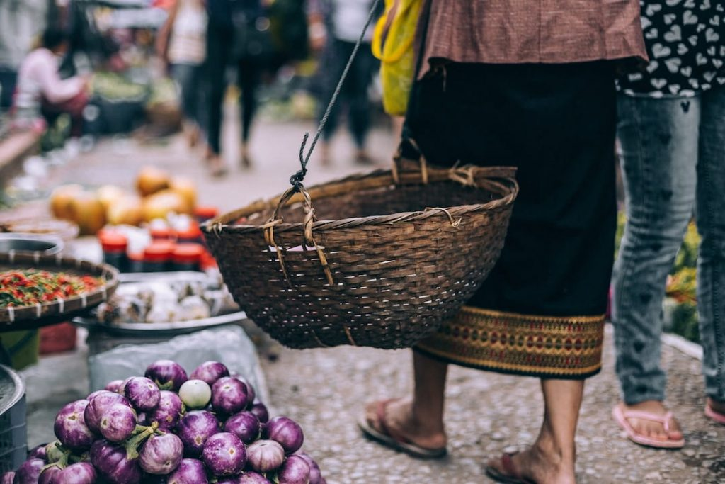 A low angle shot of a woman with a basket in a market in Luang Prabang, Laos
