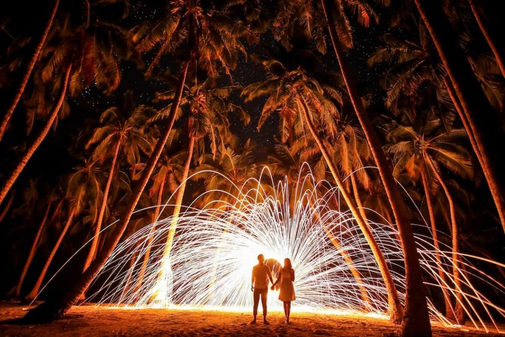 A couple hold hands in front of a burst of light