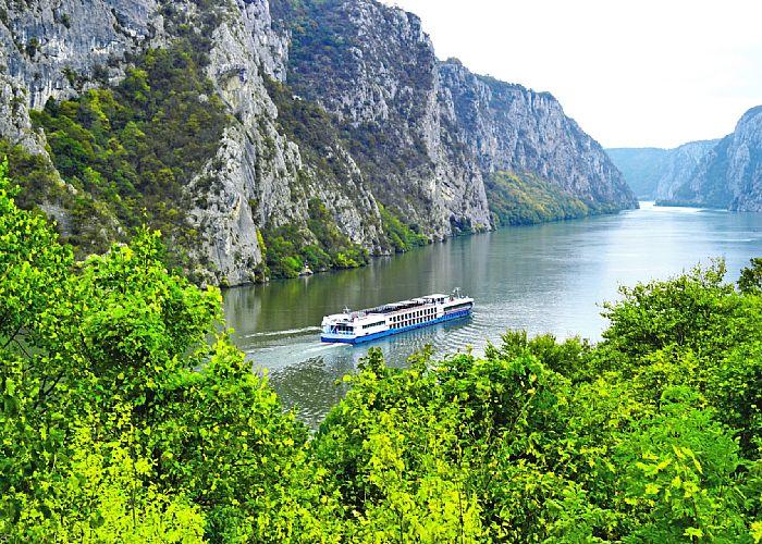 A river cruise ship sails through a valley