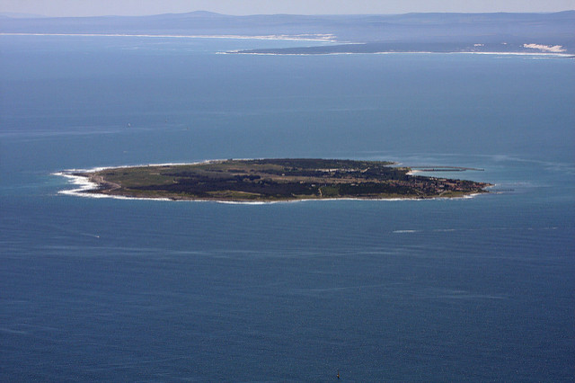 View of Robben Island from a far surrounded by the sea
