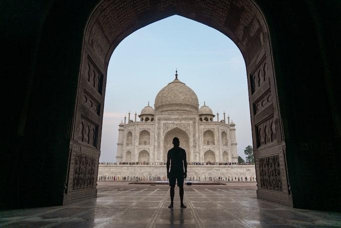 A man standing under an arch near the Taj Mahal