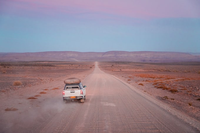 A car driving down a dirty road towards Fish River Canyon, Namibia