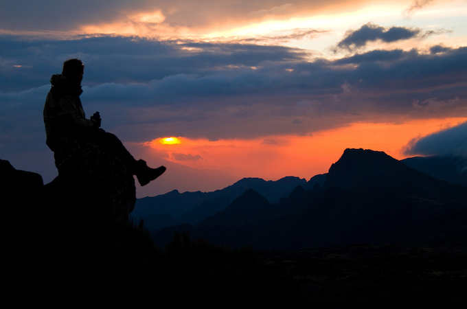 A man sitting on a rock at sunset on mount Kilimanjaro