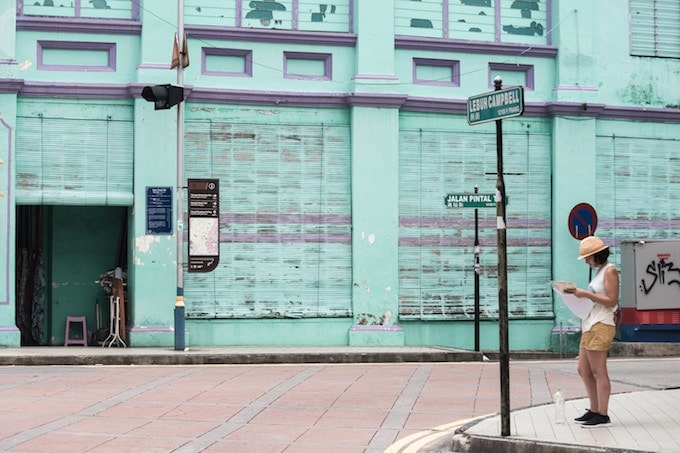 A woman stands reading a map on a street corner in George Town, Malaysia