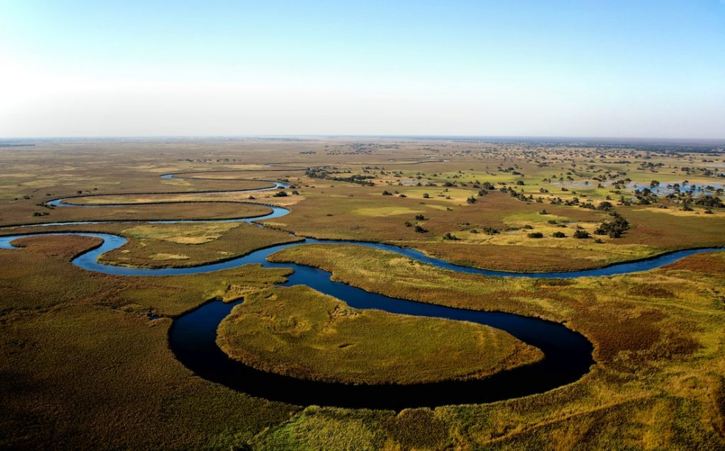 aerial photography of body of water snaking through grasslands