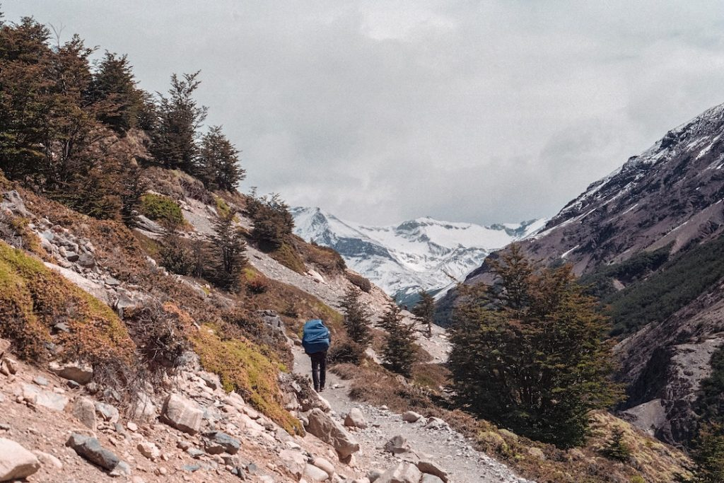 man in blue jacket hiking along a trail with snowcapped mountains in the background
