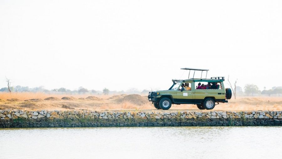 A safari truck travelling alongside a body of water in Africa