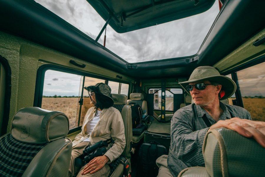 Two people in a safari truck wearing safari gear