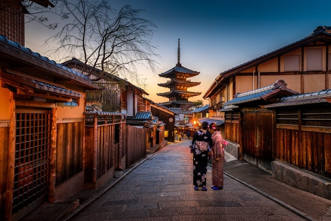 Two women in traditional clothing stand by a temple in Kyoto