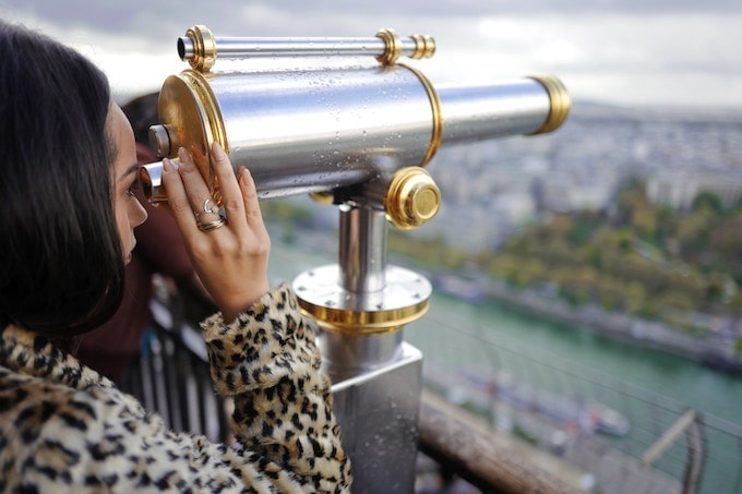 A woman looking through a telescope in Paris