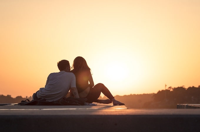 A man and woman sitting beside each other at sunset
