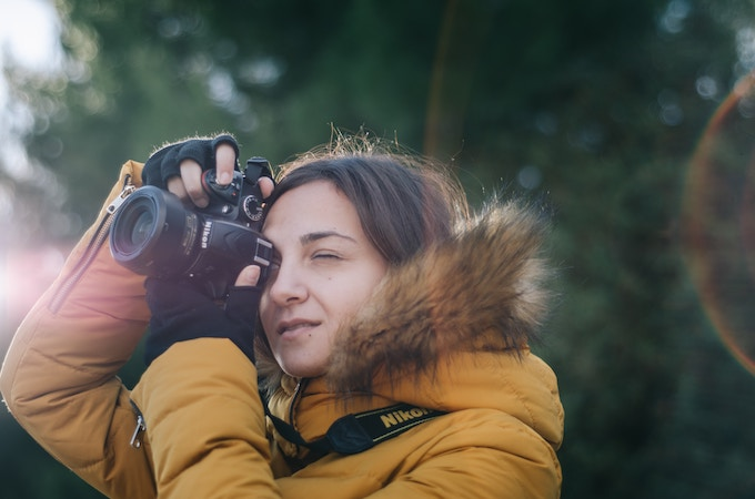 A woman in a yellow coat looks through the lens of a nikon camera
