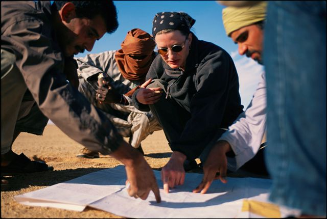 a woman and three guides look at a map in desert surroundings