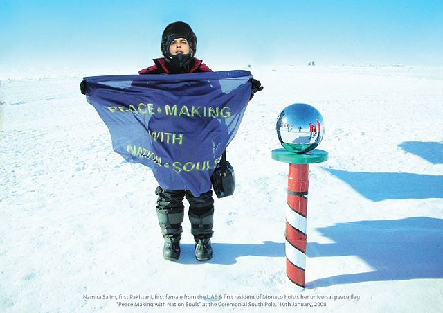 a women in a snow suit holds up a flag beside the south pole