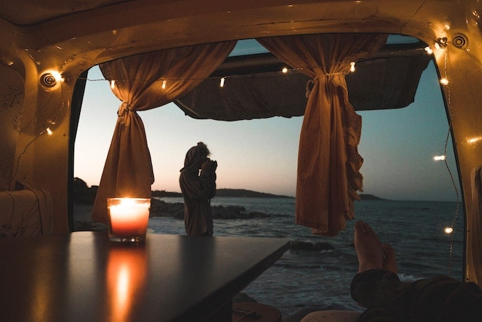 The view from the back of a van with the windows opened; the ocean and christmas lights hanging around the van