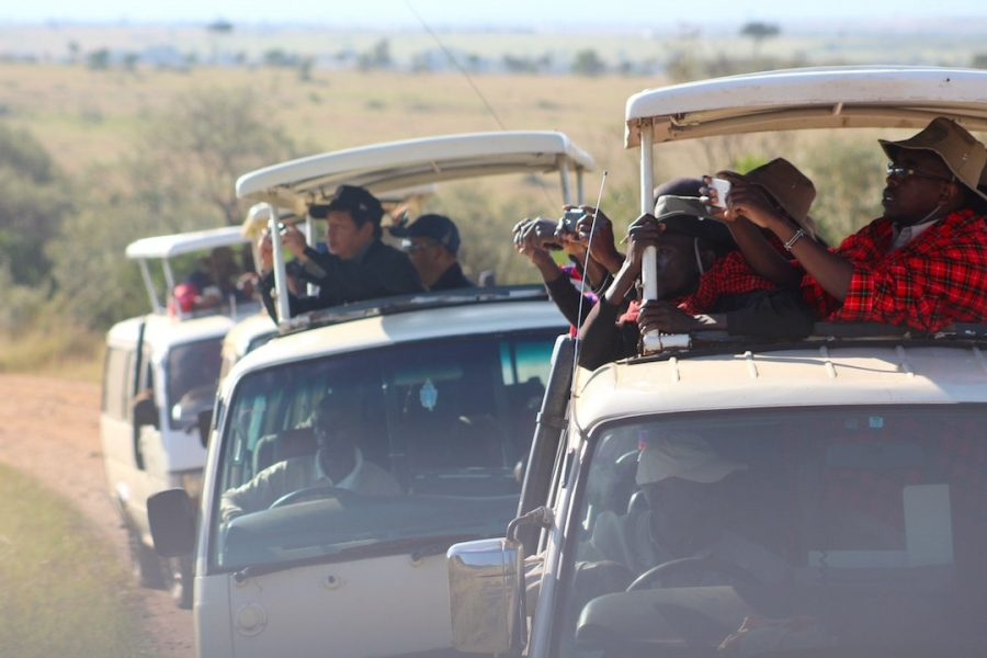 People reaching out of a safari truck to capture a photo in Kenya