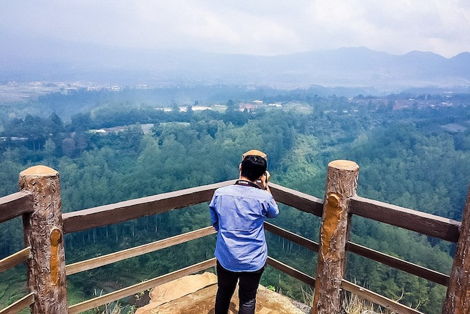 A man stands and takes a photo off a look-out point in Indonesia