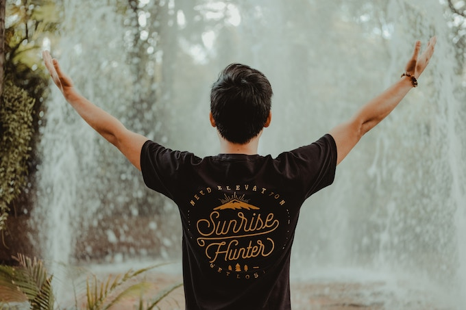 A man opening his arms in front of a waterfall in Bangkok, Thailand