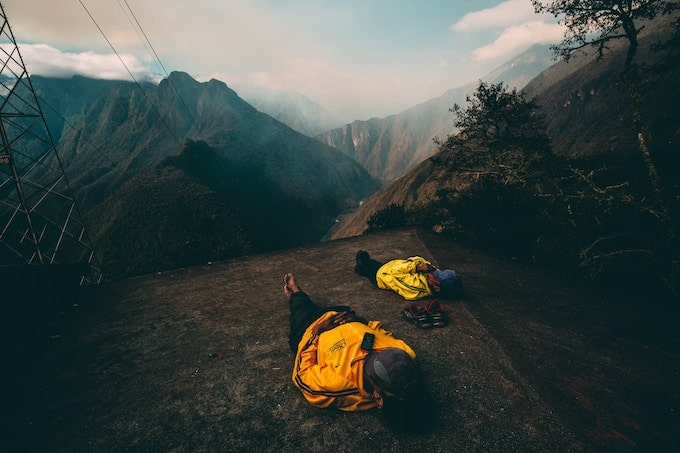 Two people in yellow jackets laying down on the Ica Trail