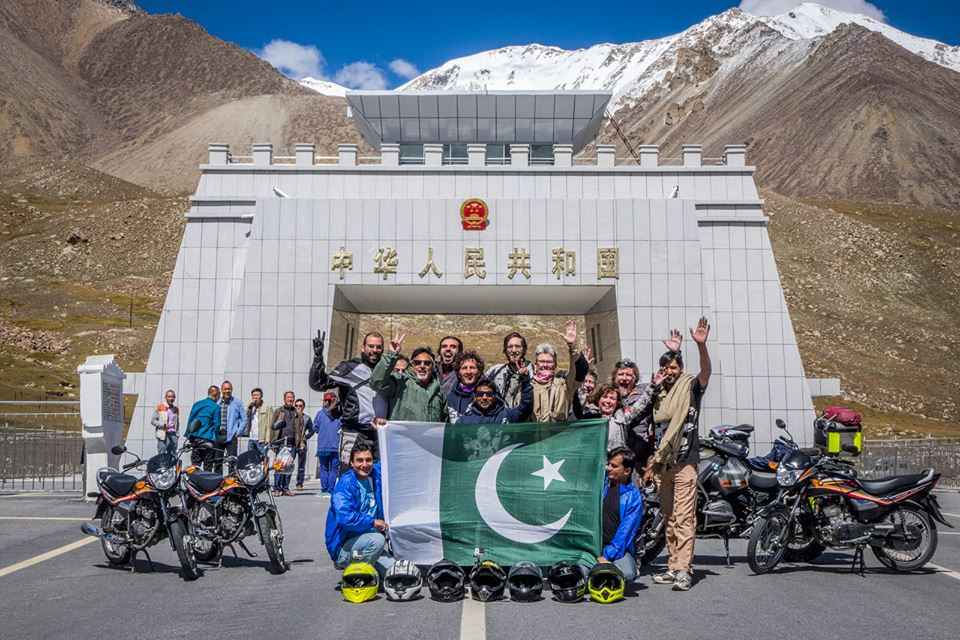 a group of people stand in front of an arch holding a green and white flag waving at the camera