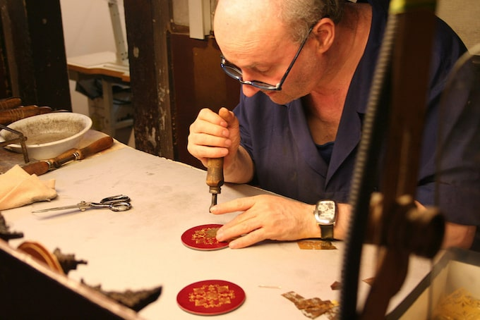 A leatherworker carves patches in Florence