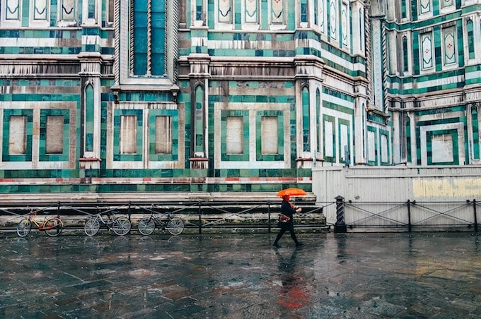 A person with an orange umbrella in front of a blue building in Florence, Italy