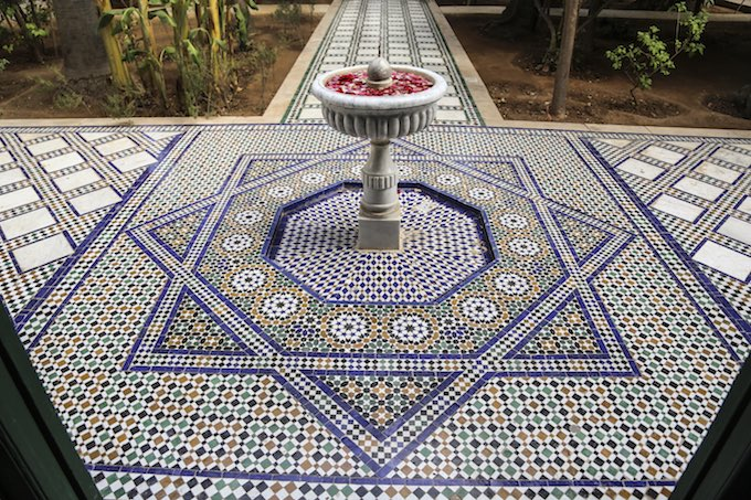 Traditional yard in a riad in Morocco with mosaic tiles floor and a fountain with petals