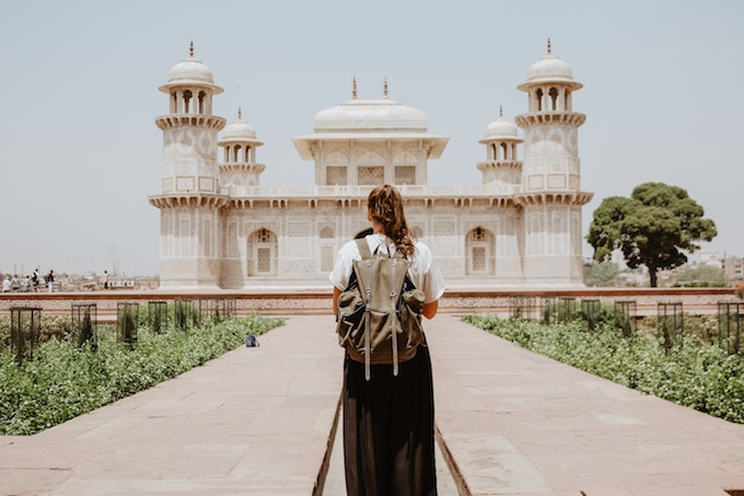 A woman with her back to the camera stands in front of a tomb in Agra, India