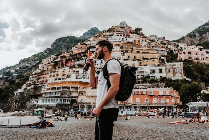 A man drinking a glass bottle of coke in positano, Italy