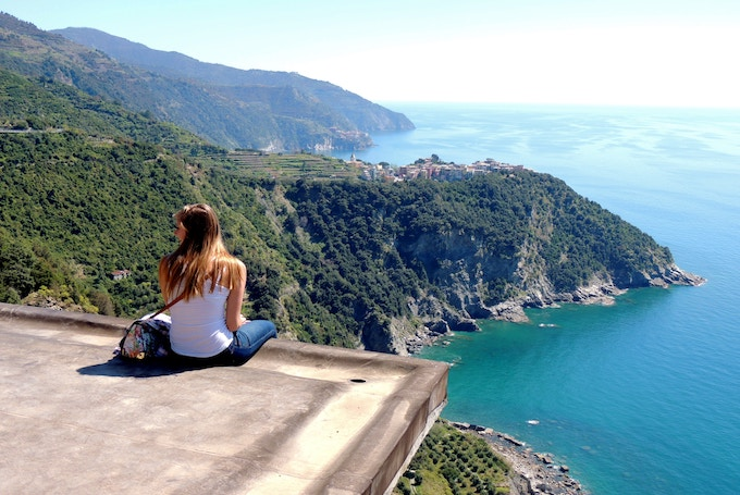 A woman sitting on a ledge in Cinque Terre, Italy
