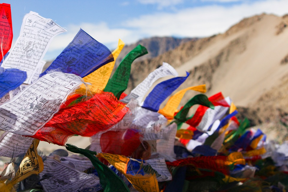 colourful holy flags in blue, white, reg, green and yellow fluttering in the wind