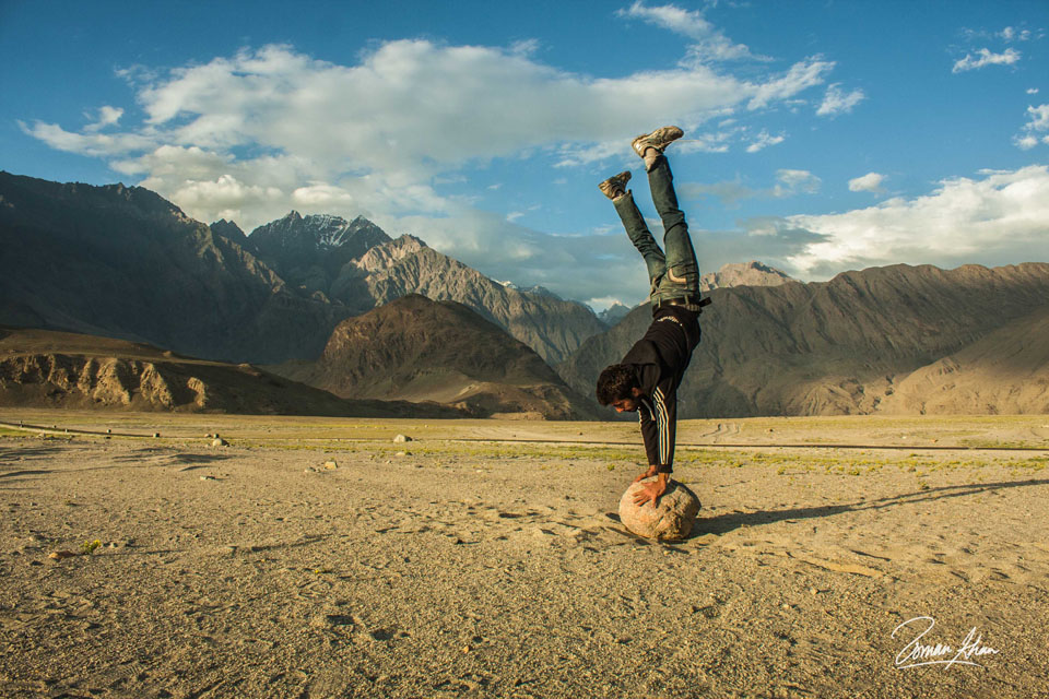 A man doing a handstand on the rocks with the mountains in the background in the north of Pakistan