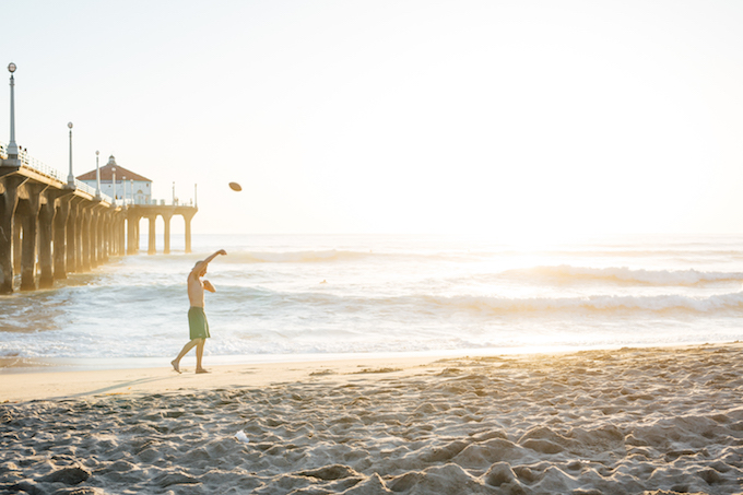 a man walking a beach throwing the ball in the air