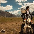 a shot of man on his motorbike looking back at the mountains of pakistan