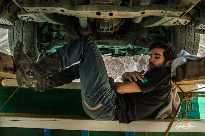 a man relaxing under a truck, looking very cool, with a pakistani flag on his t-shirt