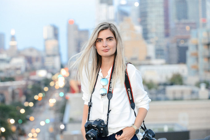 a woman in a white shirt with a camera around her neck with a city scape in blurred in the background