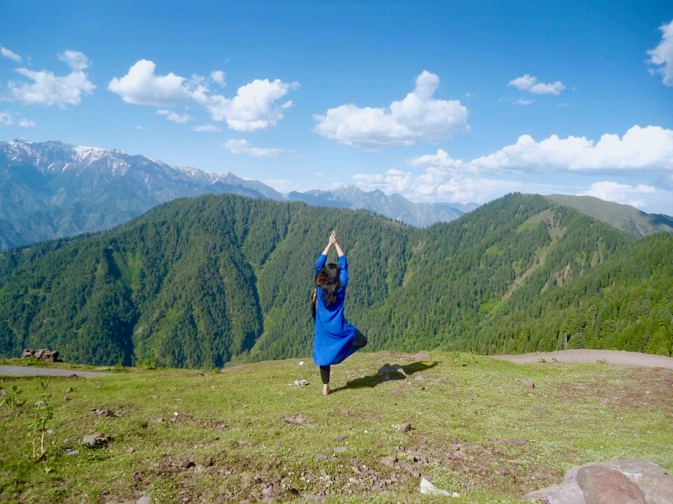 a woman doing a tree pose on a mountain top