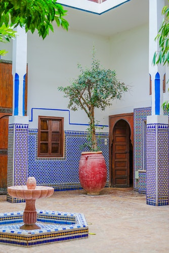 a colourful riad with tile work, plants and a small arabic fountain